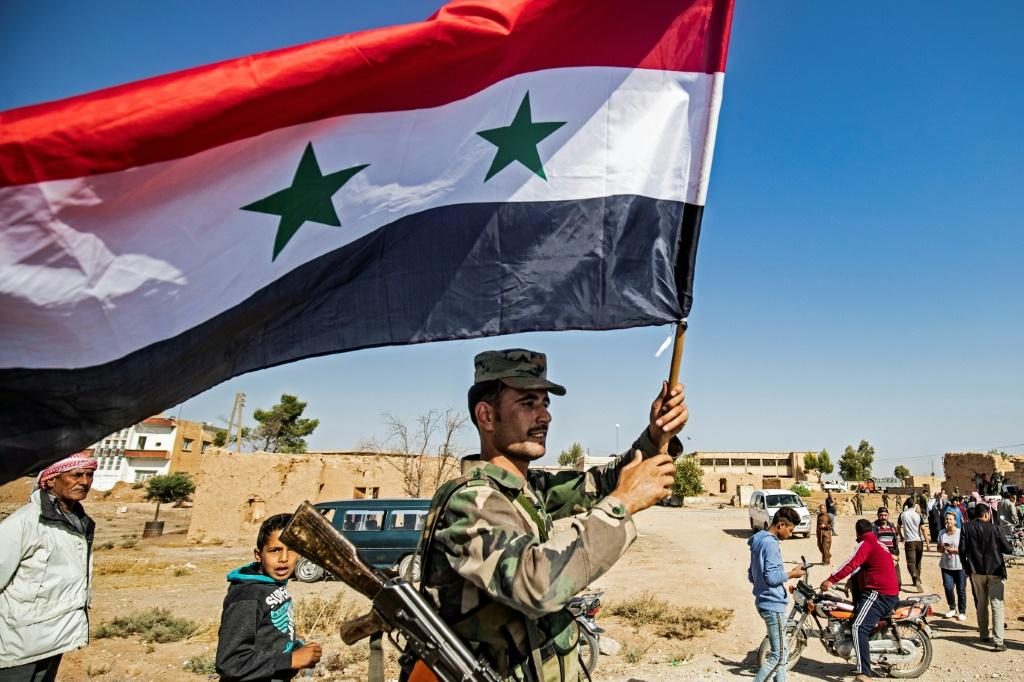 A Syrian regime soldier waves the national flag in the town of Tal Tamr as Damascus deploys forces towards the Turkish border
