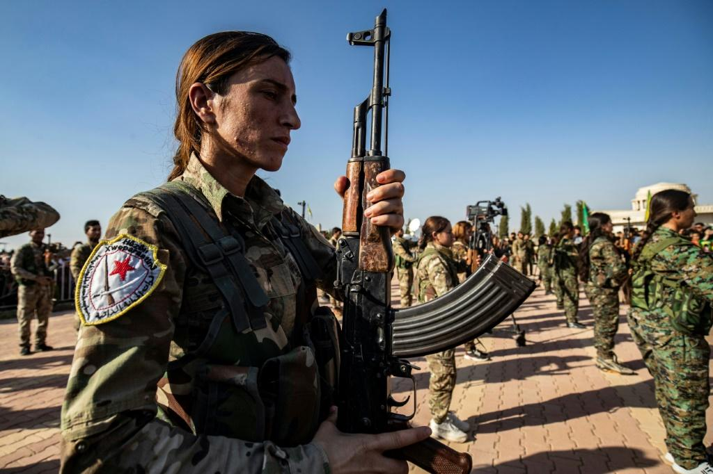 Kurdish forces attend a funeral for a political leader and others killed in the Turkish offensive