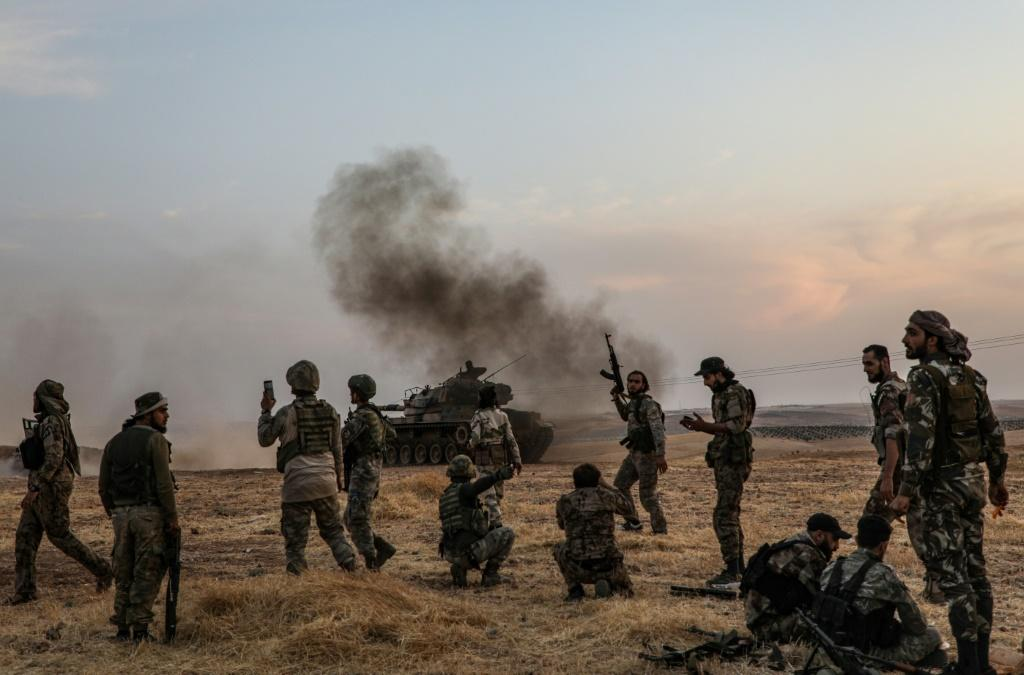 Turkish soldiers and Turkey-backed Syrian fighters gather on the northern outskirts of the Syrian city of Manbij