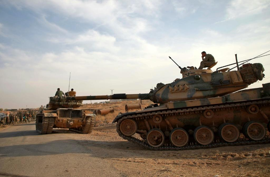 Turkish troops with American-made M60 tanks move near the village of Qirata in Syria