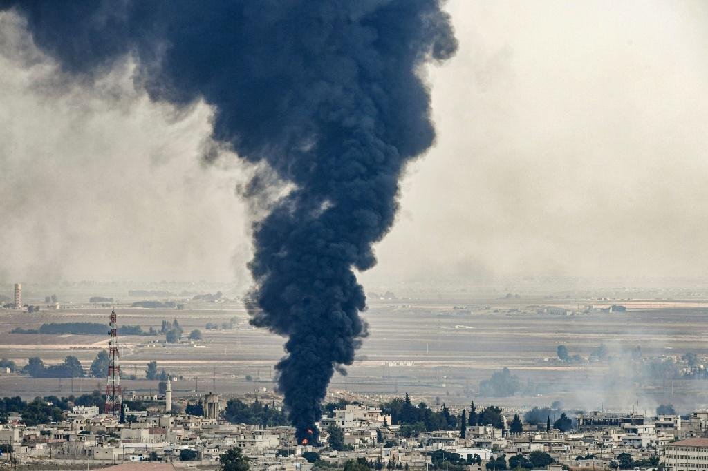 Smoke rises from the Syrian border town of Ras al-Ain whre tyres burn in a bid to blind Turkish warplanes as clashes continue across the region