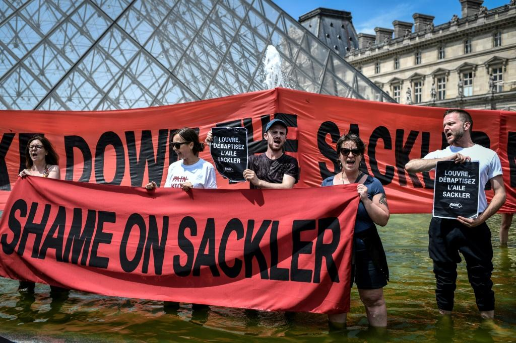 Activists outside the Louvre Museum in Paris protested on July 1, 2019 against the museum's links to the Sackler family, major philanthropists, because of their ownership of Purdue Pharma and links to the opioid crisis