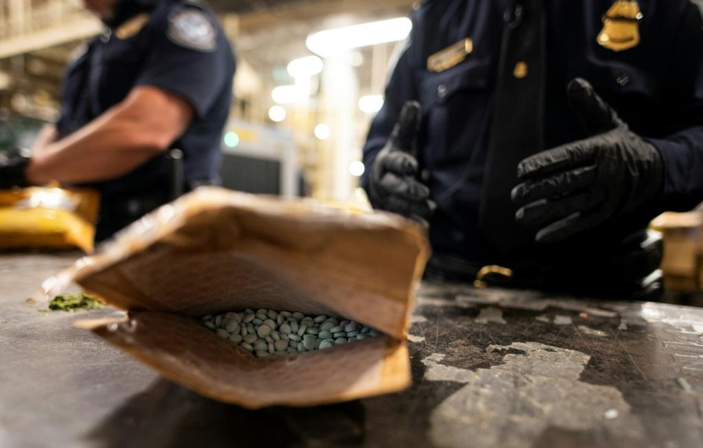 A packet of pills marked oxycodone is opened at New York's JFK airport -- the postal facility is staffed day and night to sift through packages for suspicious contents