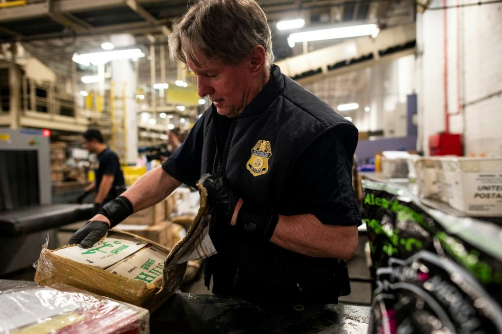 A US customs officer finds pills stamped with oxycodone during a package detection operation at John F. Kennedy Airport in New York