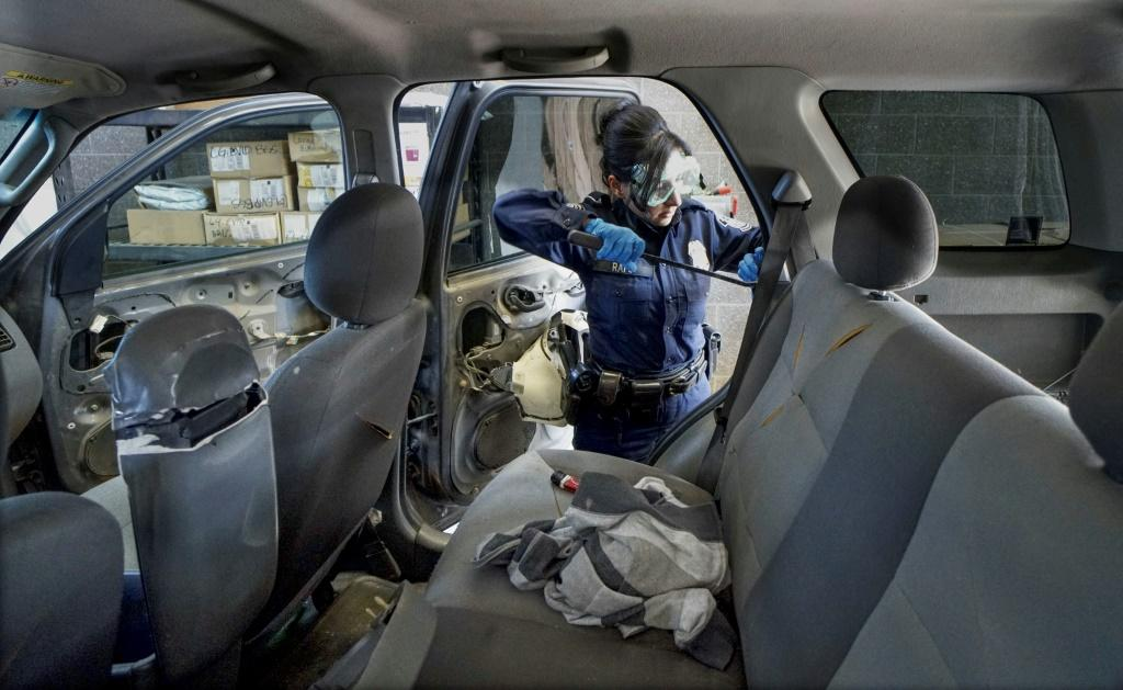 A US customs officer looks for drugs in a vehicle at California's San Ysidro border crossing on October 2, 2019