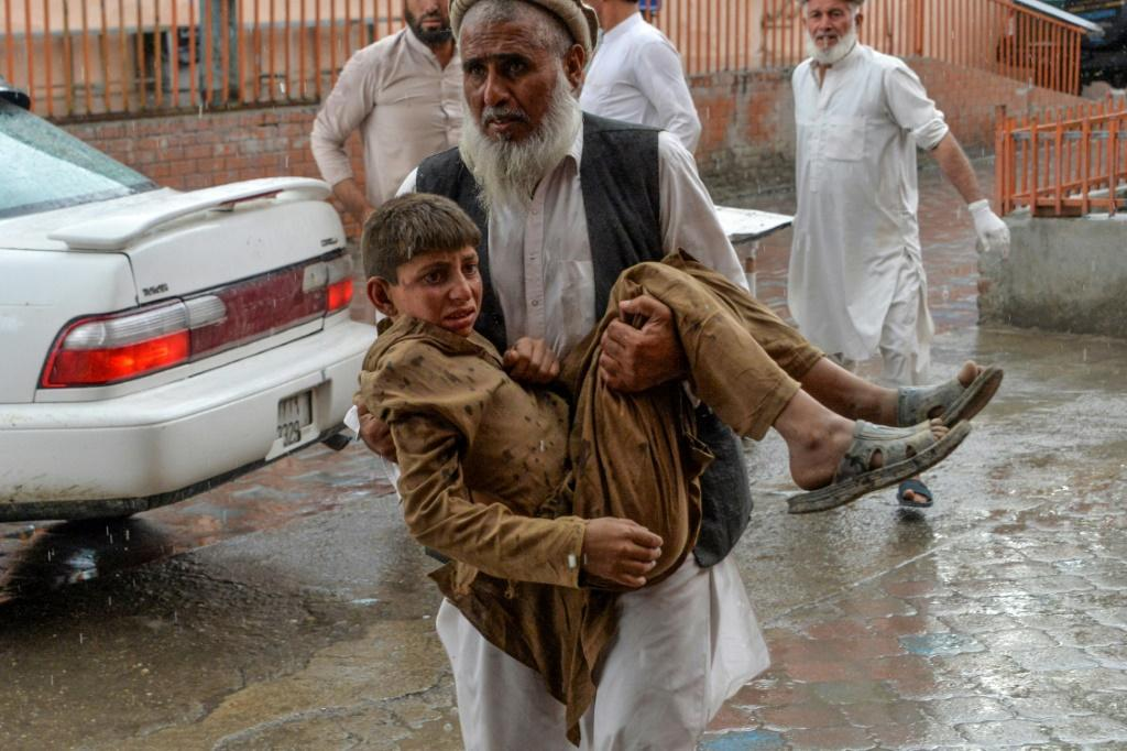A volunteer in Afghanistan carries an injured youth to hospital following the country's second-deadliest blast of the year, in Nangarhar Province