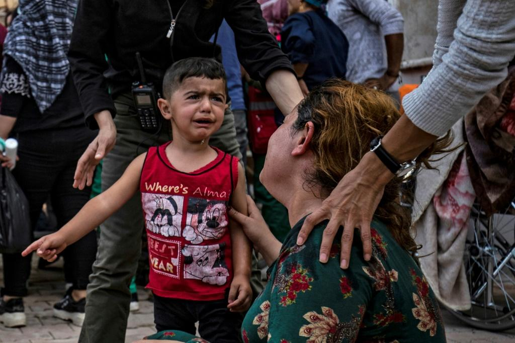 A woman and a child react as the body of a man killed during Turkish shelling near the Syrian Kurdish town of Ras al-Ain arrives at a hospital in the nearby town of Tal Tamr