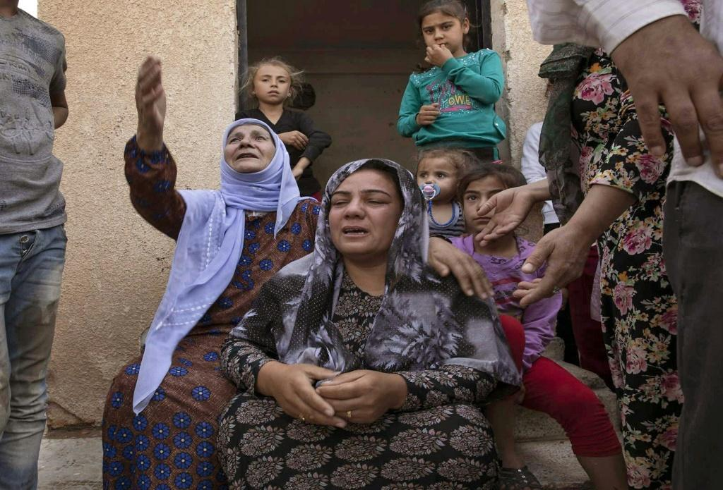 Women react during the Turkish offensive against Kurdish-controlled areas of northeastern Syria in Tal Tamr, near the Syrian Kurdish town of Ras al-Ain