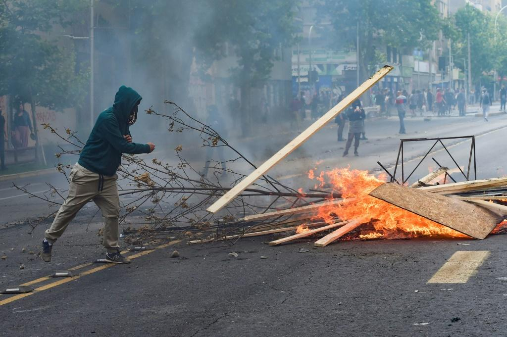 Demonstrators set up barricades during clashes between protesters and the riot police in Santiago, Chile on October 19, 2019