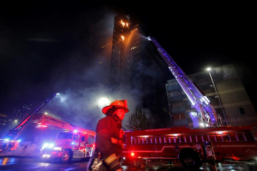 Firefighters tackle the blazing ENCEL building, which was set alight during protests in downtown Santiago