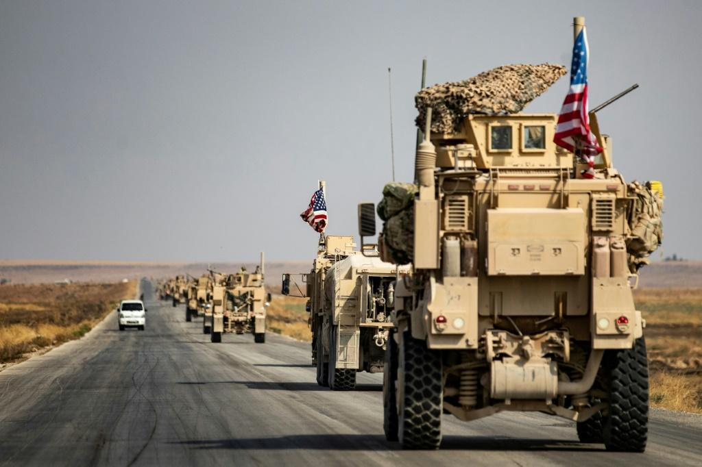 Dozens of US armoured vehicles escorted by helicopters were seen driving through northern Syria