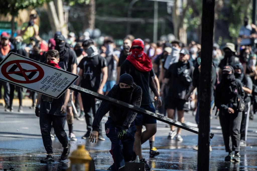 Demonstrators clash with riot police during a protest in Santiago, on October 21, 2019