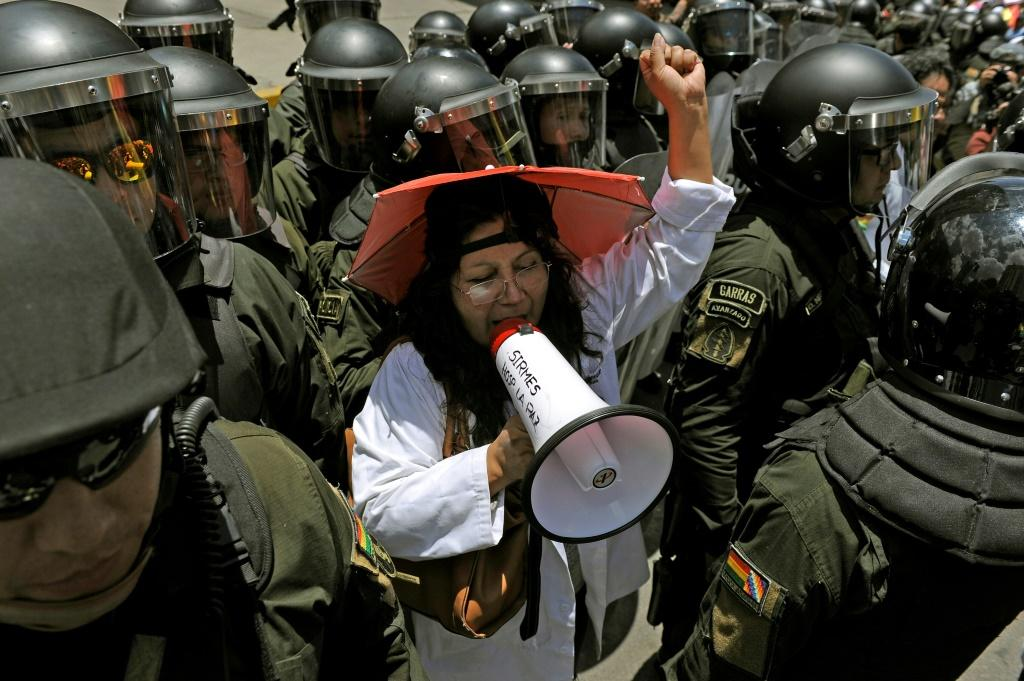 A health worker is surrounded by security forces as she protests outside the headquarters of the election authority in Bolivia's capital La Paz