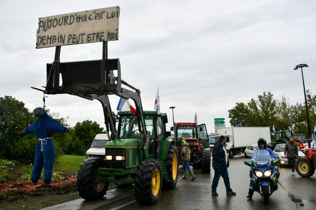 """A tractor with a hanged effigy of a farmer under a sign saying """"Today it's him, tomorrow it might be me,"""" during a protest by farmers in Nimes, southern France, on Tuesday."""
