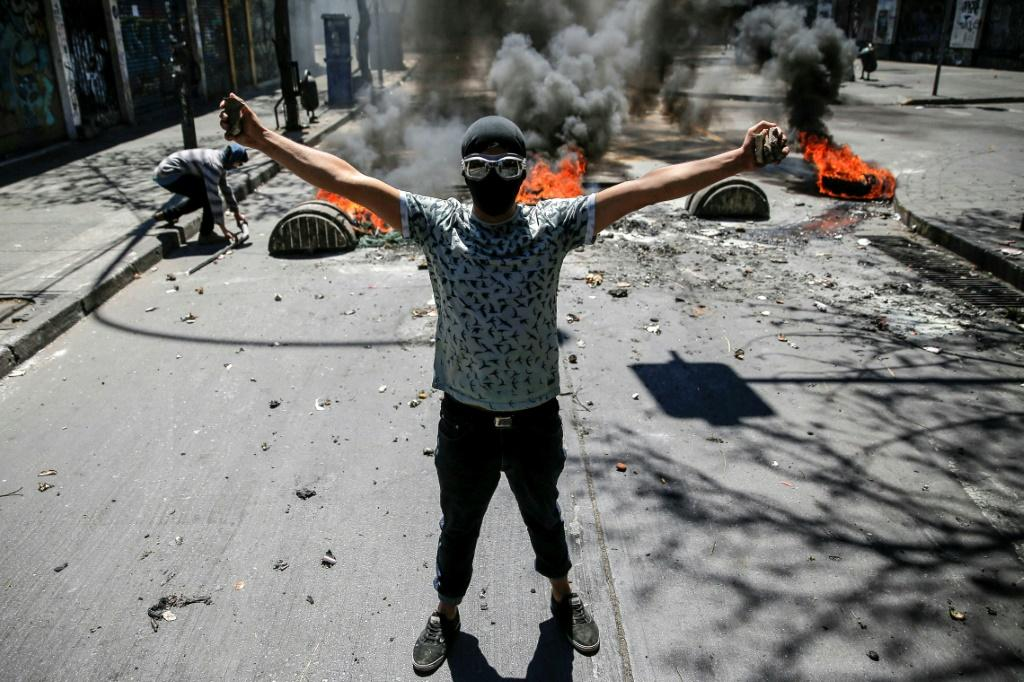 Demonstrators clash against soldiers during a protest in Valparaiso, Chile, on October 21, 2019