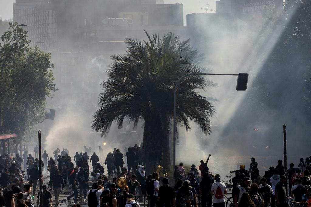 Demonstrators clash with riot police during protests in Santiago, on October 20, 2019