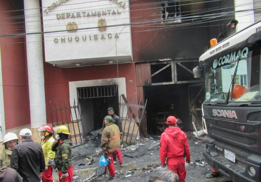 Firefighters survey the wreckage of the electoral authority headquarters in the southern city of Sucre after poll results that appeared to hand victory to incumbent president Evo Morales sparked riots