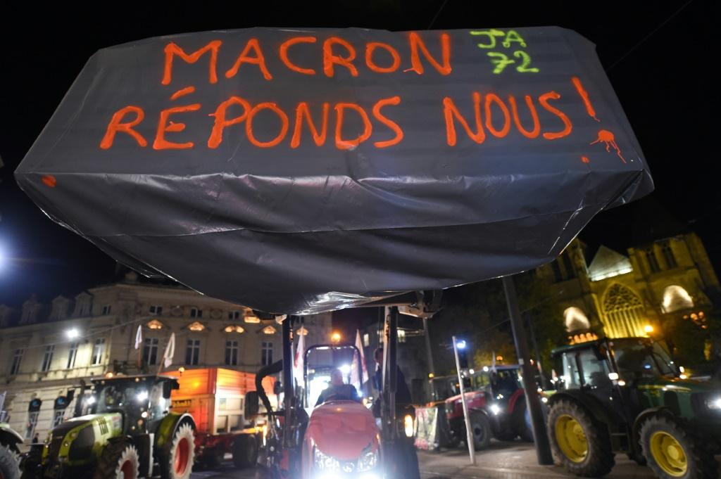 """Tractors with a sign saying """"Macron, answer us!"""" as farmers began a protest on Monday in Le Mans, western France."""