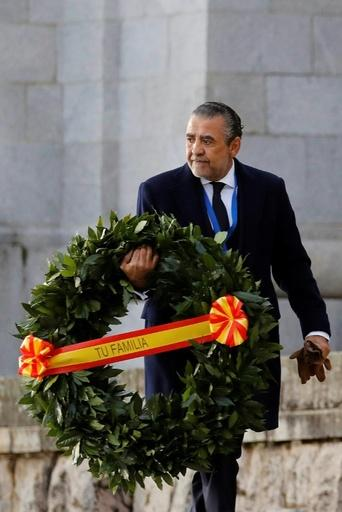"Franco's grandson, Jaime Martinez Bordiu, carries a wreath with a ribbon saying ""Your family"" as he arrives for the exhumation"