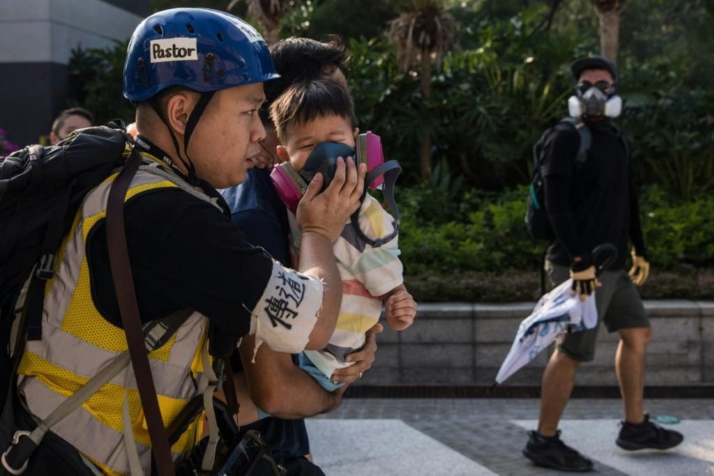 A man puts a gas mask on a young boy after police fired tear gas to disperse protesters, the latest clashes in nearly five months of unrest