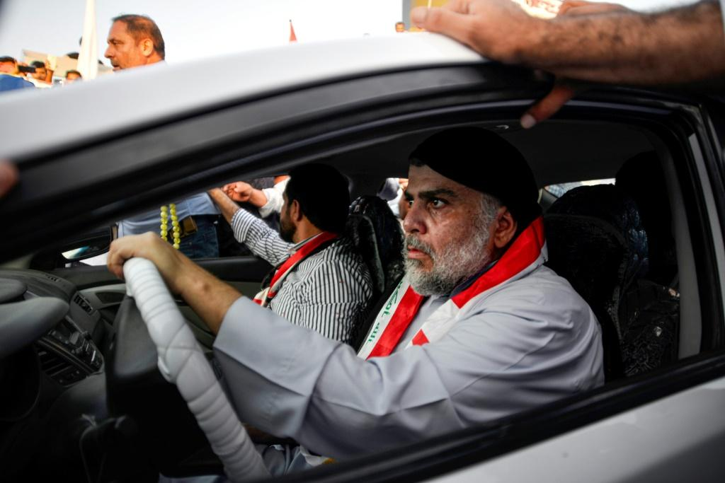 Populist Shiite cleric Moqtada al-Sadr (driving) has backed anti-government protests despite being a key part of the administration
