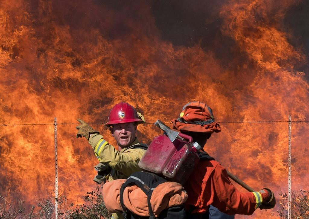 A firefighter (L) speaks to an inmate firefighter as they prepare to put out flames on the road leading to the Reagan Library during the Easy Fire in Simi Valley, California on October 30, 2019