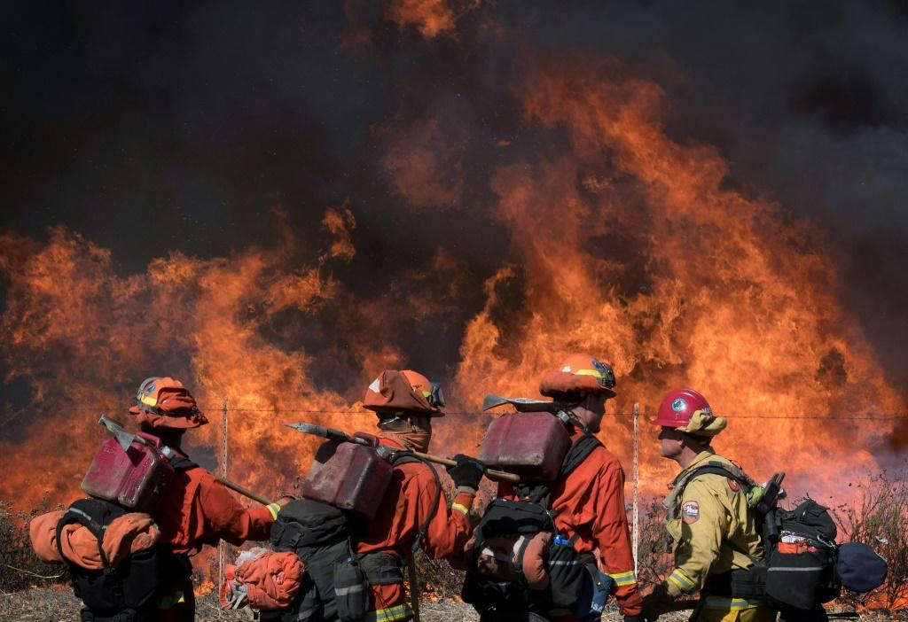 Firefighters walk the road leading to the Reagan Presidential Library during the Easy Fire in Simi Valley, California on October 30, 2019
