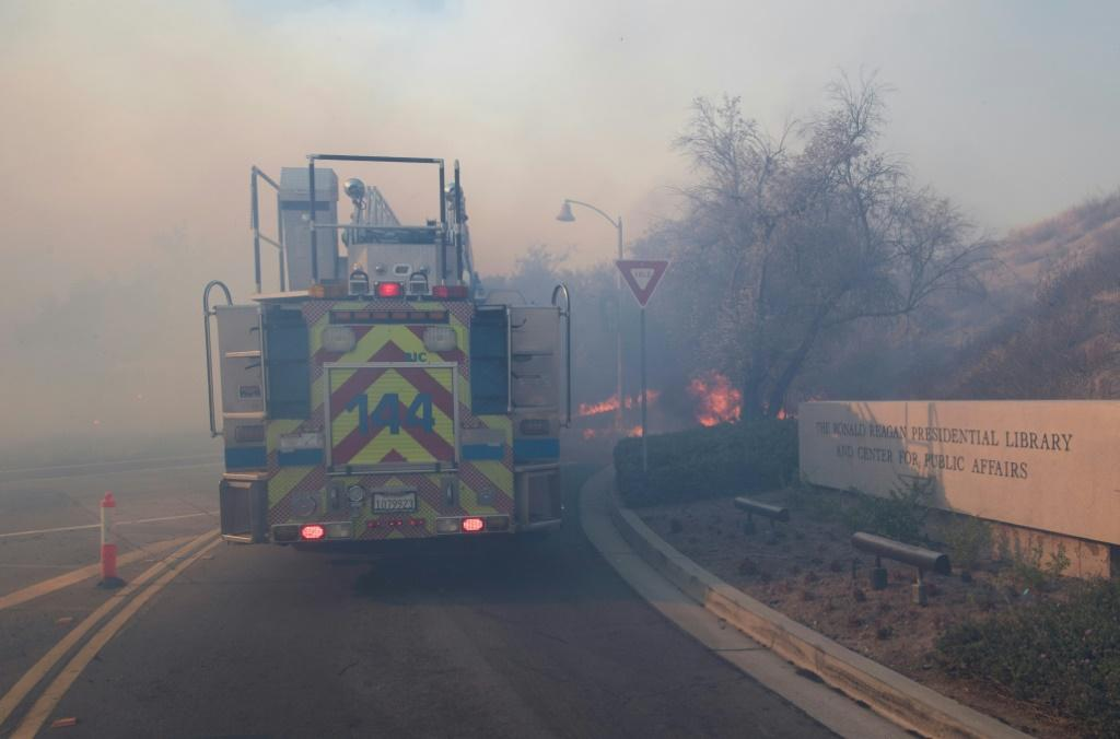 Flames cross the driveway of the Reagan Presidential Library as firefighters battle to protect it from the Easy Fire in Simi Valley, California on October 30, 2019