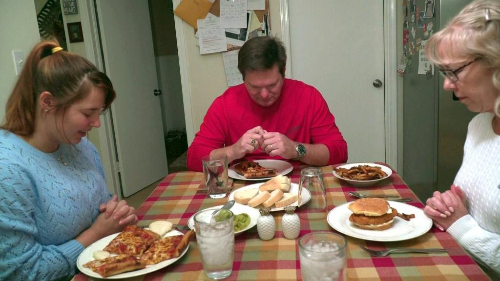 In this still image taken from video, autoworker Mike Yakim prays with his wife Sara and their niece, Haley (L), before dinner on October 16, 2019, in Lordstown, Ohio, where US President Donald Trump garnered unexpected support in 2016