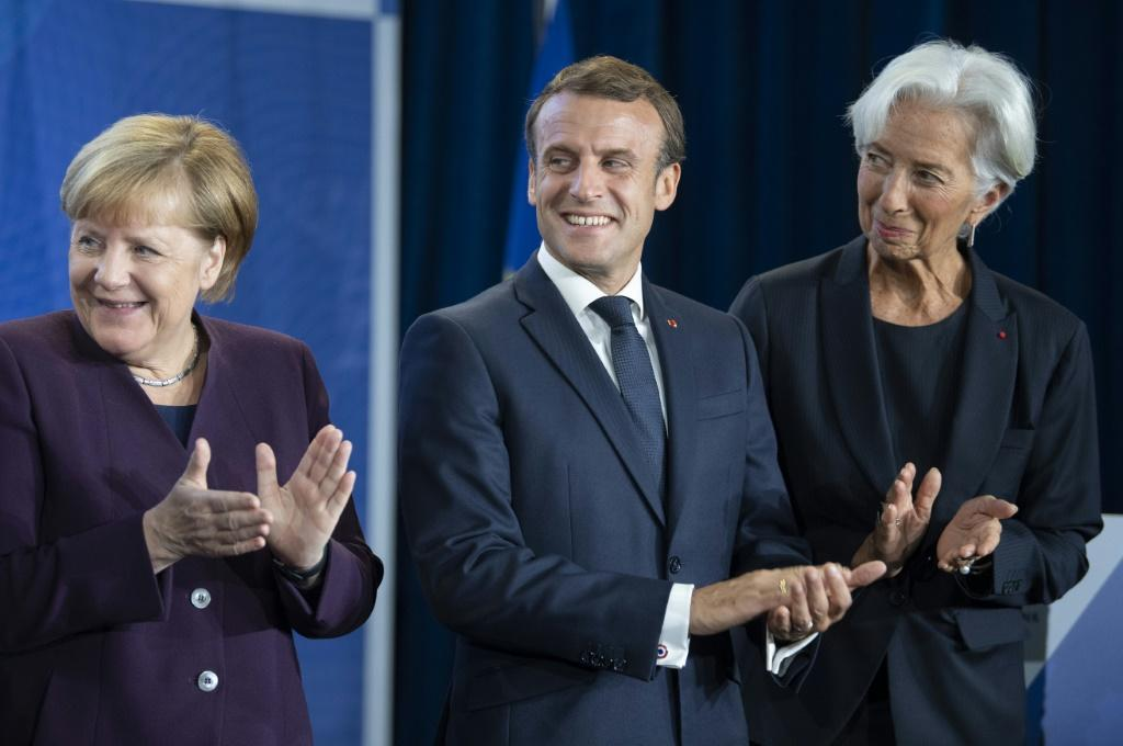New ECB head Christine Lagarde (right) wants Germany Chancellor Angela Merkel (left) to increase public spending to give the sluggish European economy a boost, a move supported by French President Emmanuel Macon (centre)