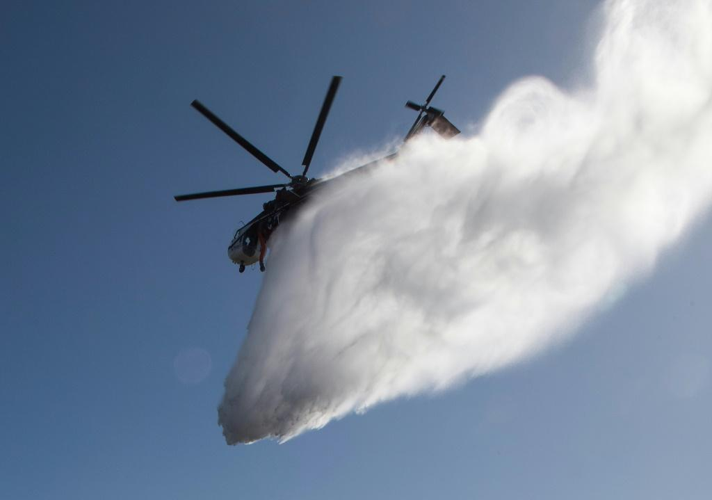 Water dropped by a helicopter lands on flames burning near the Reagan Library during the Easy Fire in Simi Valley, California on October 30, 2019