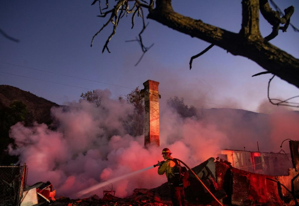 A firefighter douses a smoldering home during the Hillside Fire in the North Park neighborhood of San Bernardino, California on October 31, 2019.