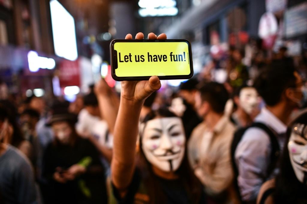A masked Halloween reveller flashes a phone message to police in the Lan Kwai Fong entertainment area of Hong Kong