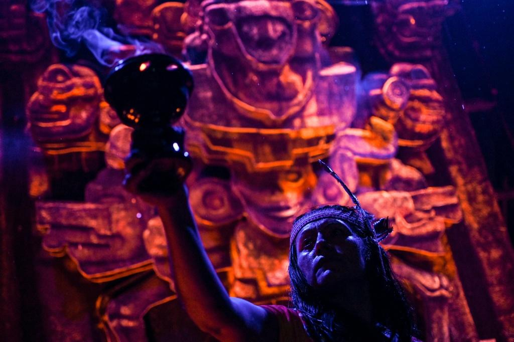 """Actors perfom in front of an altar dedicated to the underworld at the """"Gran Ofrenda"""" (Mega Offering) installed in the Chapultepec Forest in Mexico City, for Day of the Dead"""