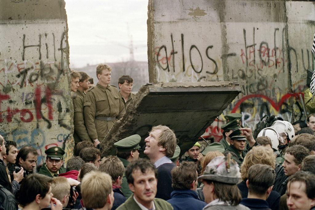 The Berlin Wall comes down in November 1989, with some East German border guards demolishing one section