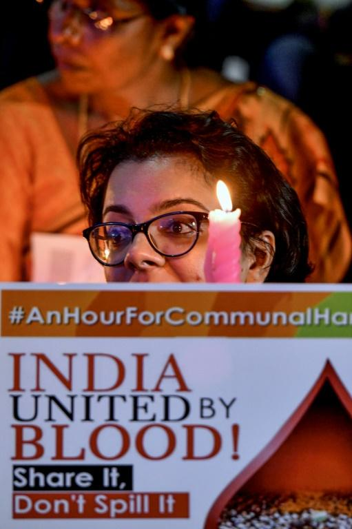 An activist belonging to 'People for Peace and Justice' holds a placard as she participates in a candlelight vigil in the Indian city of Bangalore ahead of the Ayodhya verdict