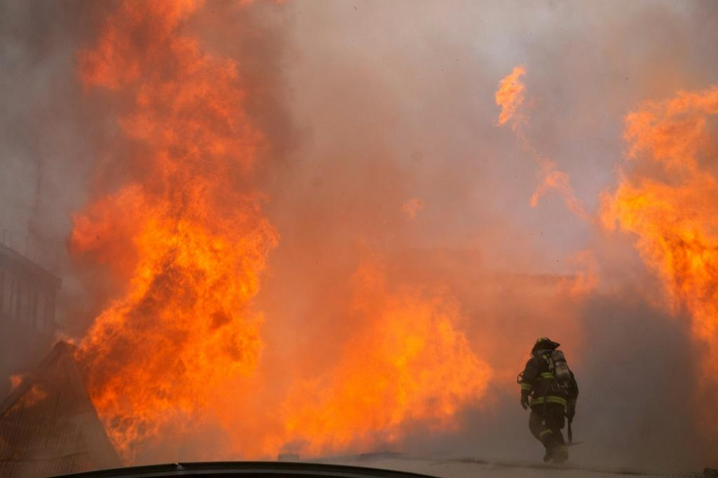 Firefighters work to extinguish a fire at Pedro de Valdivia University following a protest against the government of Chilean President Sebastian Pinera in Santiago, on November 8, 2019