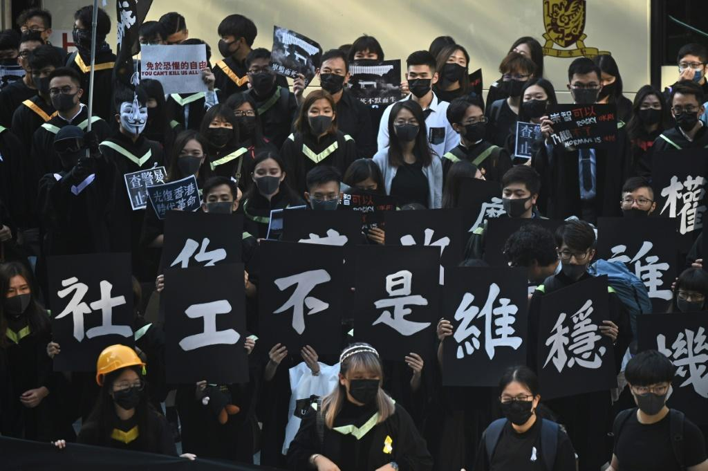 Masked university students protest against Chin's rule of Hong Kong at their graduation ceremony