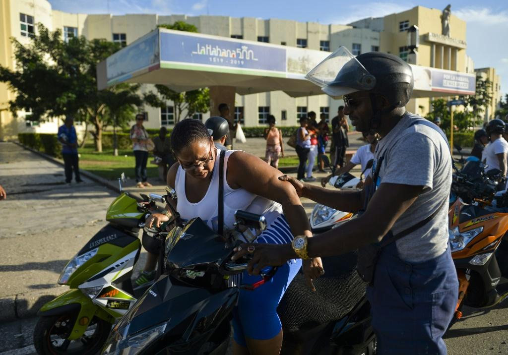 Members of the Electric Motorcycles of Cuba club ride passengers home