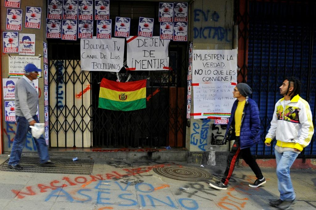 "People walk past the closed entrance of state TV channel BoliviaTV, plastered with pictures depicting President Evo Morales as a clown and calling him a ""fraud"" on November 9, 2019, in La Paz"