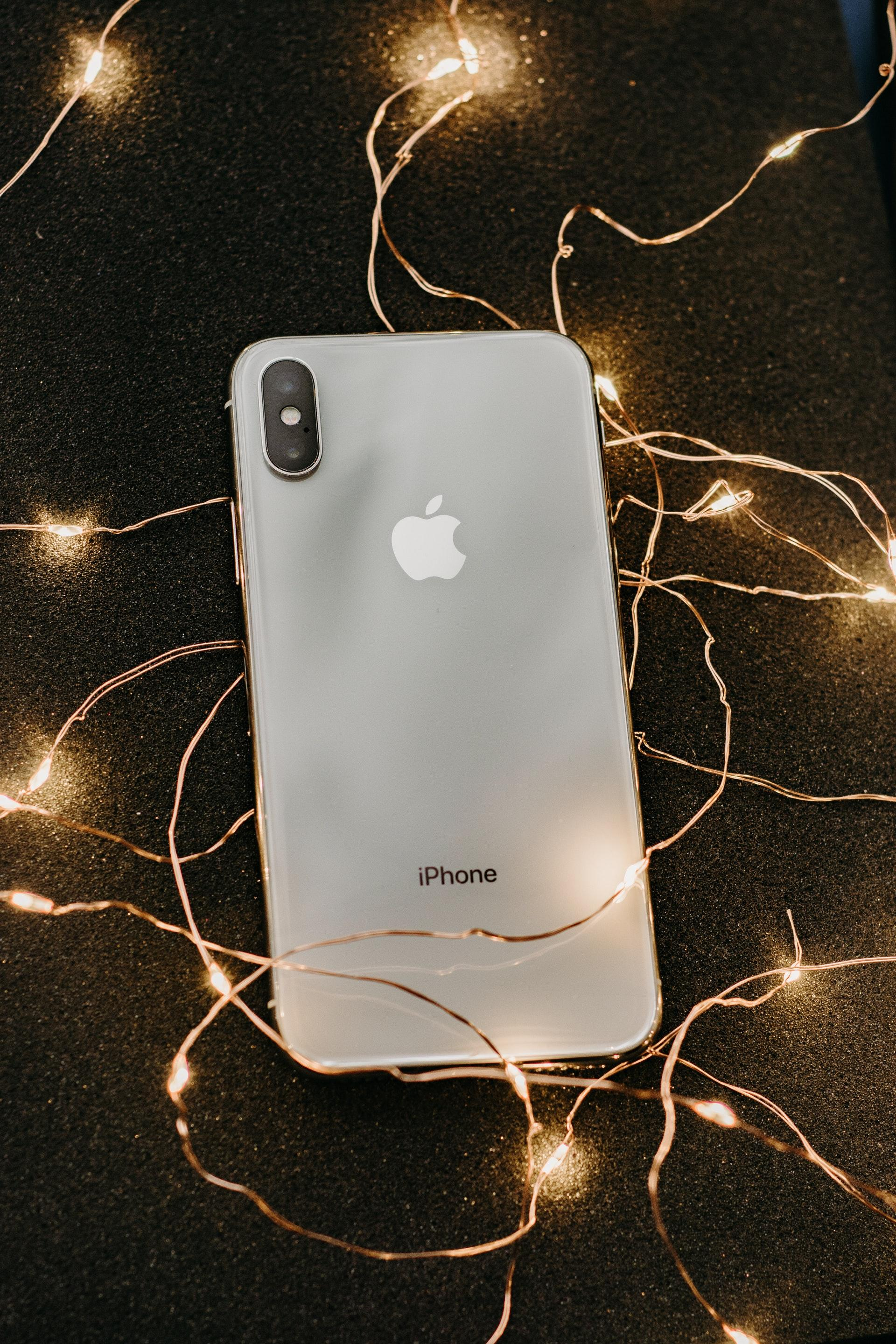 silver-iphone-x-lying-on-pre-lit-string-lights-1647976