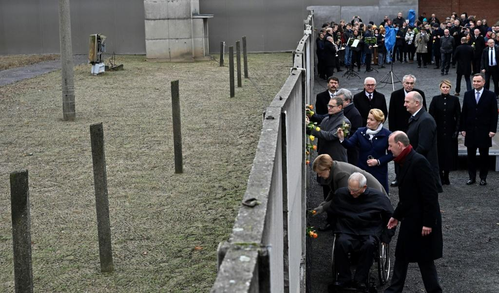 Under grey skies, German leaders and those from Poland, Hungary, Czech Republic and Slovakia put roses through cracks in part of the Wall that still stands