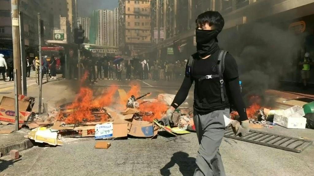 IMAGESFlashmob protests spring up in multiple Hong Kong districts during the morning commuter period, with small groups of masked protesters building barricades on road junctions.