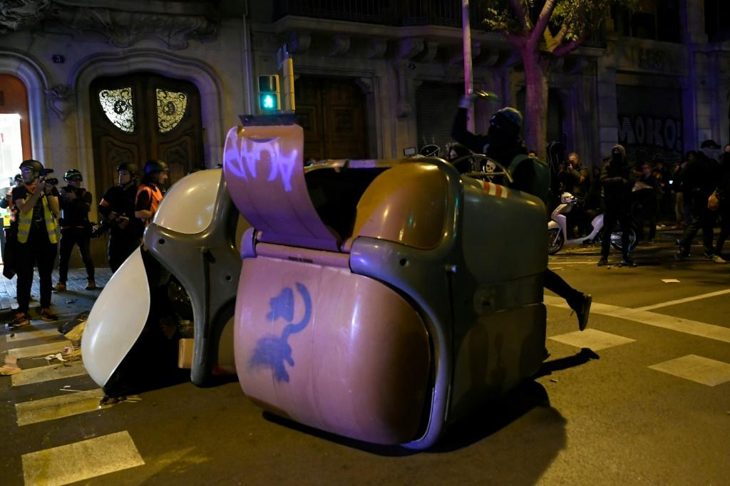 Protesters throw objects during a demonstration in Barcelona on the even of Sunday's election, amid heightened tensions over the Catalan crisis