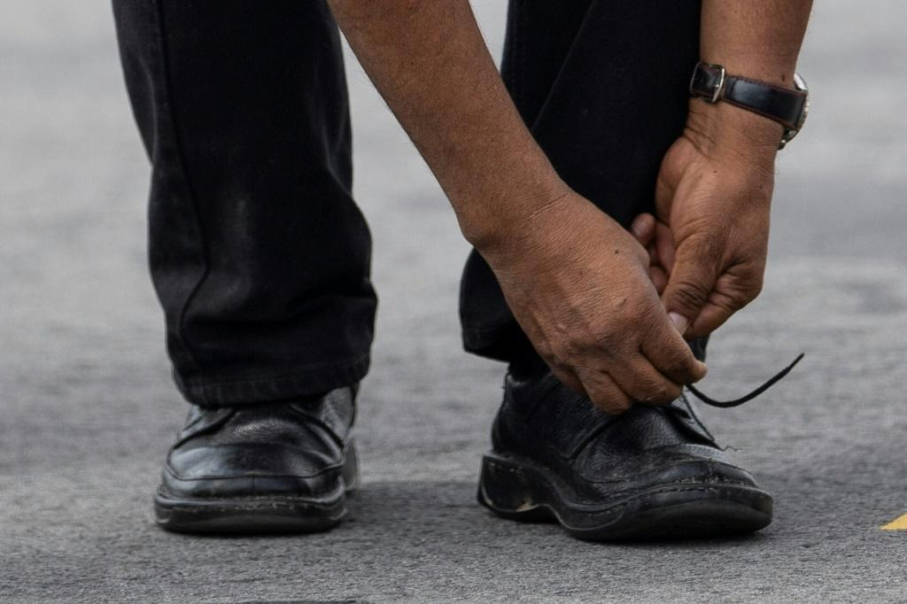 Bolivian ex-President Evo Morales ties his shoe upon landing in Mexico City, on November 12, 2019, where he was granted asylum after his resignation
