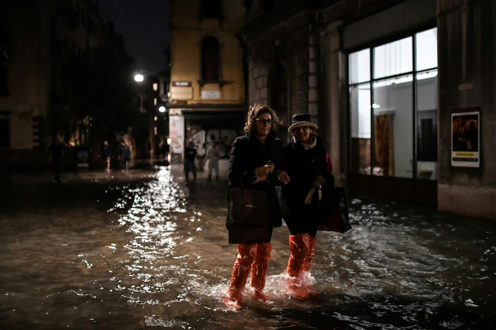 "People cross a flooded street during an exceptional ""acqua alta"" on November 12 in Venice"