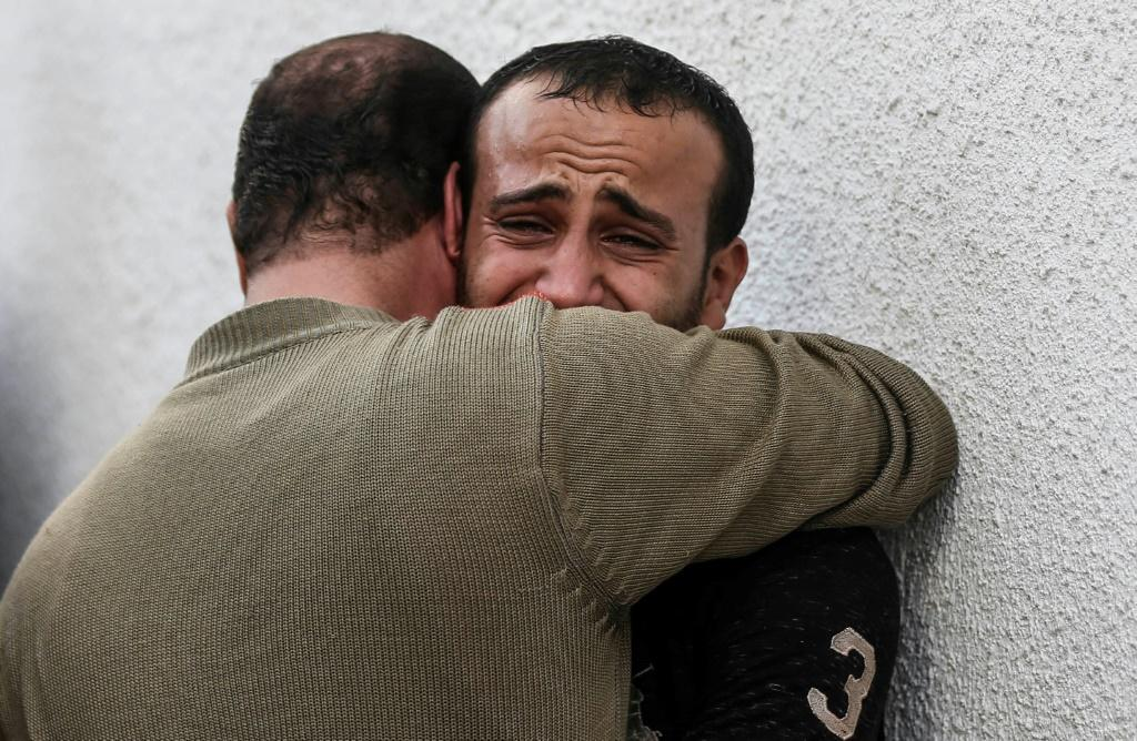 Palestinian men mourn outside the mortuary of Al-Shifa hospital in Gaza City as the death toll from Israeli strikes tops 20