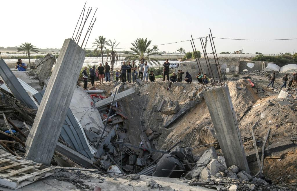Palestinians gather around the remains of a house destroyed in an Israeli air strike on the city of Khan Yunis in the southern Gaza Strip