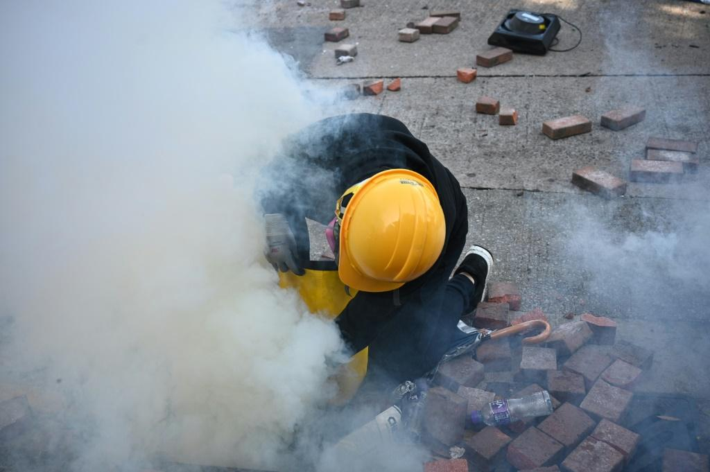A protester attempts to snuff out a tear gas canister fired by police