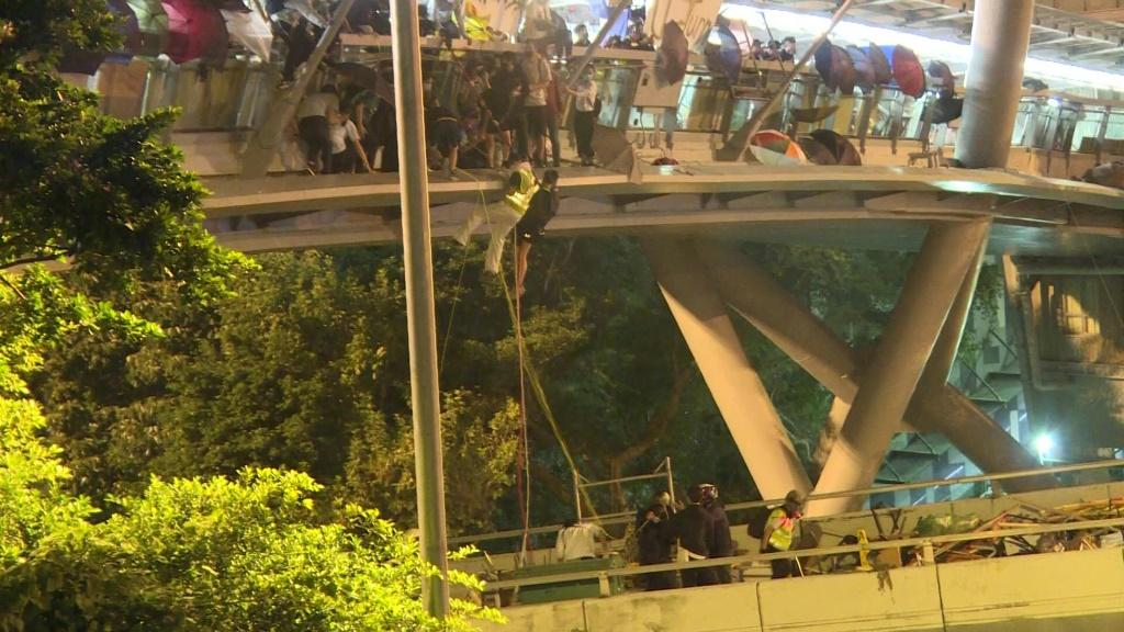 Dozens of Hong Kong pro-democracy protesters dramatically escape a police siege at a university campus by shimmying down ropes from a bridge to waiting motorbikes.